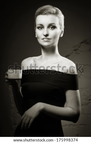 Retro styled fashion portrait of a woman with a cup of coffee in hand - stock photo