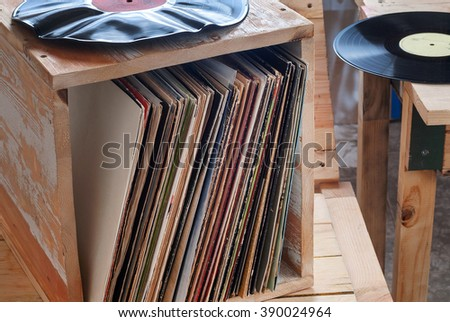 Retro styled image of a collection of old vinyl record lp's with sleeves on a wooden background - stock photo