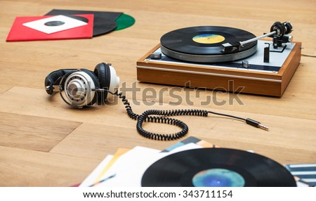 Retro styled image of a record player, vinyl LPs and a head set on a wooden surface - stock photo