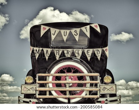 Retro styled image of a vintage car with just married decoration - stock photo