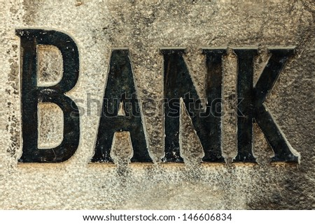 Retro styled image of an old bank sign carved in a stone wall