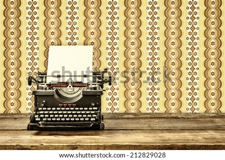 Retro styled image of an old typewriter with blank paper sheet on a wooden table with vintage wallpaper behind it - stock photo