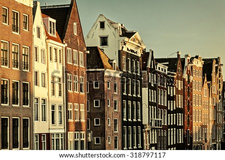 Retro styled image of ancient canal houses in the Dutch capital city Amsterdam