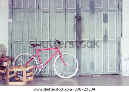 Retro styled image of pink bicycle with old wooden doors. - stock photo