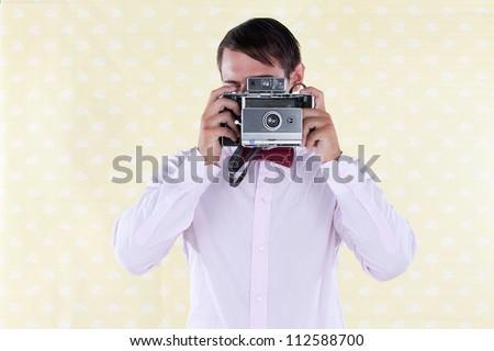 Retro styled man looking through old medium format camera - stock photo