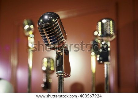 retro styled microphones against crimson wall - stock photo