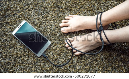 Retro styled or retro color feet tied to smartphone USB cable on turf surface. Concept of slave to technology. Slightly de-focused and close-up shot. Copy space.