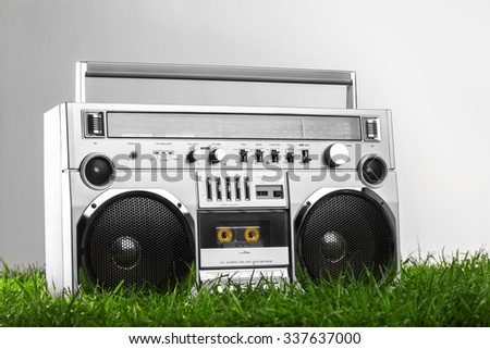 Retro-styled silver boom box over green grass isolated on gray background - stock photo