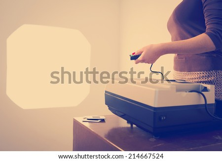 Retro styled woman operating a slide projector with a wired remote control
