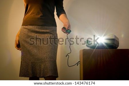 Retro styled woman operating a slide projector with a wired remote control and lens flare from projector light - stock photo