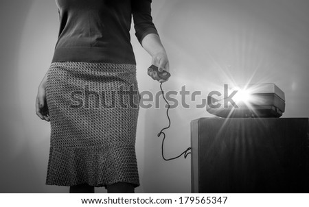 Retro styled woman operating a slide projector with a wired remote control and lens flare from projector light in black and white