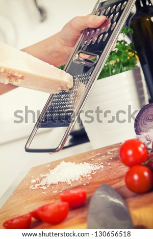 retro stylized image of ingredients for pasta and hands grating parmesan