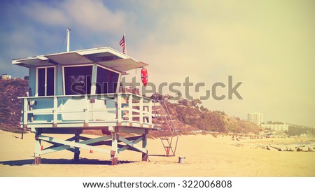 Retro stylized panoramic picture of a lifeguard tower in Santa Monica at sunset, California, USA. - stock photo