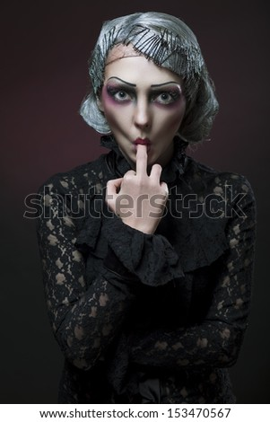 retro stylized photo of a beautiful young woman sucking middle finger