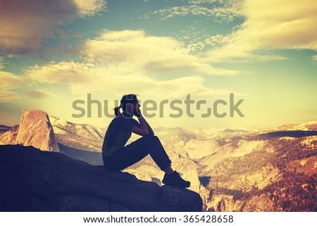 Retro stylized silhouette of a woman watching mountain view at sunset, Yosemite National Park, USA. - stock photo