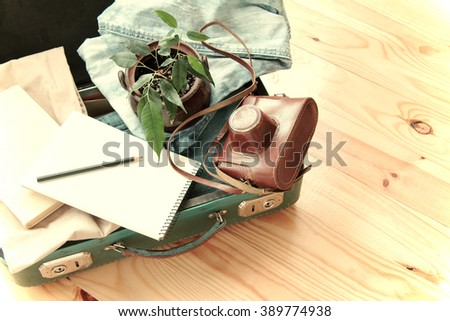 Retro suitcase with camera ficus in a pot and a notebook for sketches/retro traveler baggage - stock photo