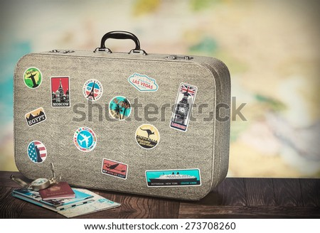 retro suitcase with stikkers on the floor against the backdrop of a world map. Toned image - stock photo