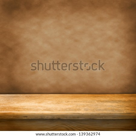 Retro table with wooden table and grunge wall - stock photo