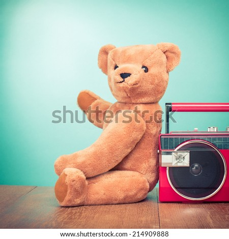 Retro Teddy Bear toy and red radio recorder front mint green background - stock photo