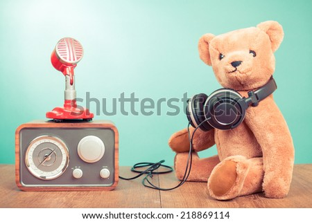 Retro Teddy Bear with headphones, radio and microphone front mint green background - stock photo