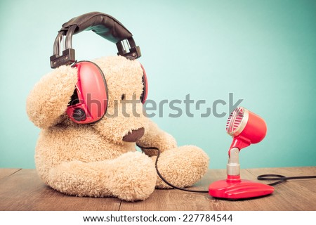 Retro Teddy Bear with old red microphone and headphones sitting front mint green background - stock photo