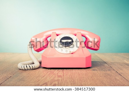 Retro telephone front mint green wall background. Old style filtered photo - stock photo