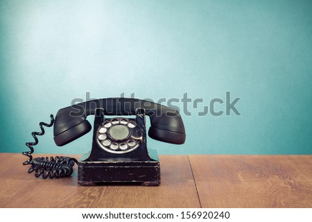 Retro telephone on table in front mint green background - stock photo