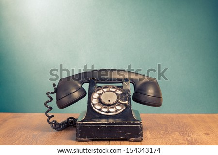 Retro telephone on wood table for old style background - stock photo