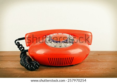 Retro telephone set on wooden table on light background - stock photo