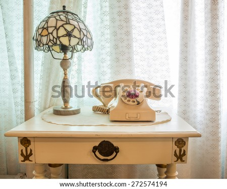 Retro telephone with vintage lamp on wood table near window background - stock photo