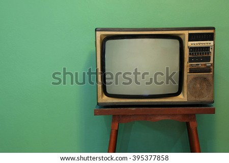 Retro television on old wooden deck with vintage green background.