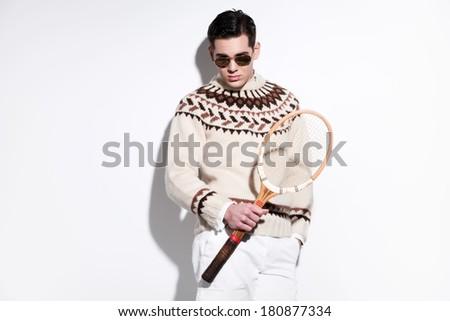 Retro tennis fashion man with sunglasses holding a vintage wooden racket. Studio shot against white. - stock photo