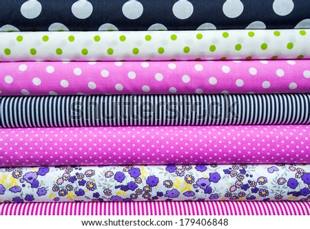 retro textiles and fabrics of different colors in the stack - stock photo