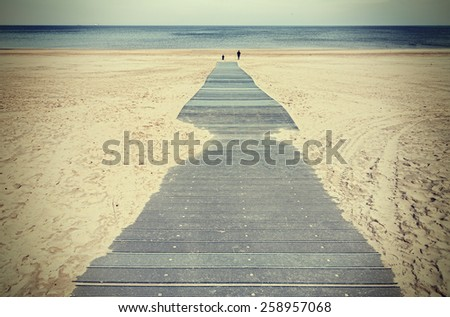 Retro toned photo of a boardwalk on beach.