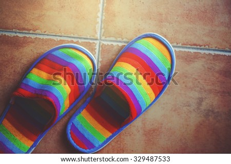 Retro toned rainbow color pattern slippers on ceramic tiled floor with natural daylight from the window, LGBT pride and coming out of closet concept, top view