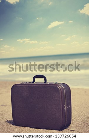 Retro travel suitcase is alone on a beach - stock photo