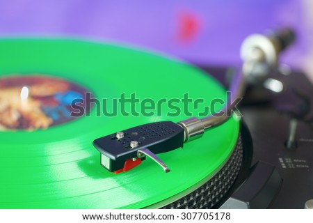 Retro turntable with green vinyl record, selective focus, fictional label artwork,free copy space - stock photo