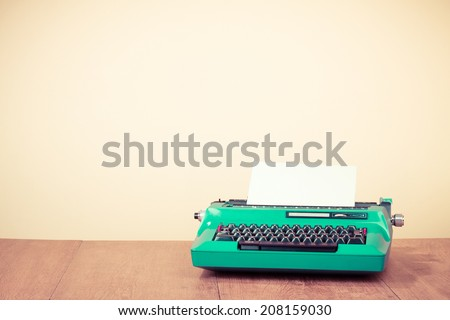 Retro turquoise typewriter on oak wooden table. Old style filtered photo - stock photo