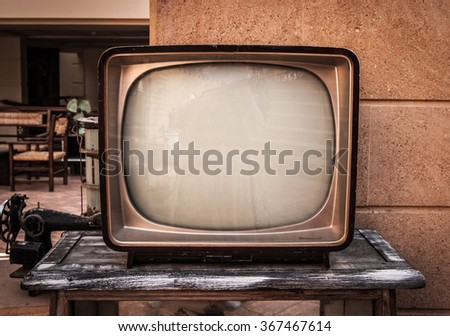 Retro TV, old television on a brick and wood background - stock photo