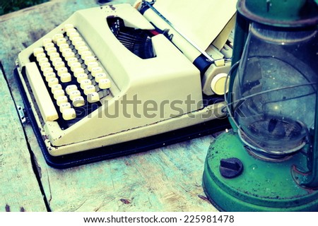 Retro typewriter with vintage lamp on wooden background - stock photo