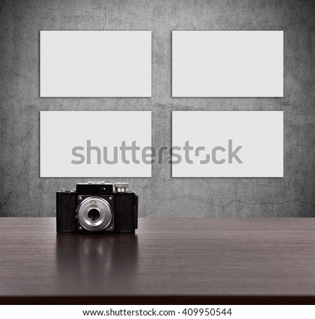Retro vintage camera on wooden table. Four blank picture on concrete wall - stock photo