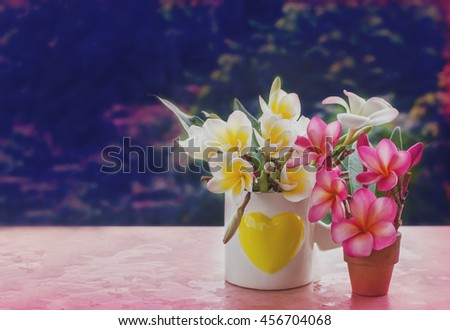 Retro vintage colour style of white pink and yellow flower plumeria or frangipani in heart pattern cup and small vase on table or shelf with blank space area background