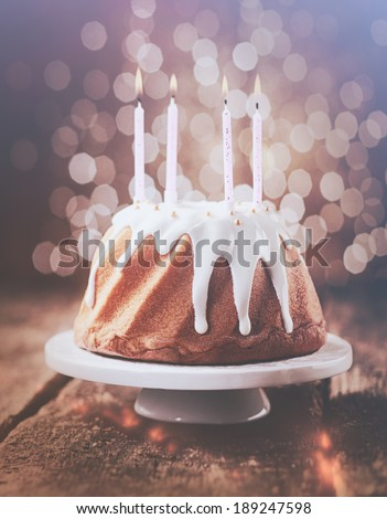 Retro vintage effect birthday cake glazed with dripping white icing decorated with pearls and topped with four burning party candles with a background bokeh of sparkling lights - stock photo