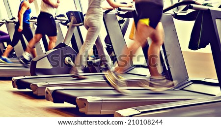 retro, vintage gym shot - people running on machines, treadmill - stock photo