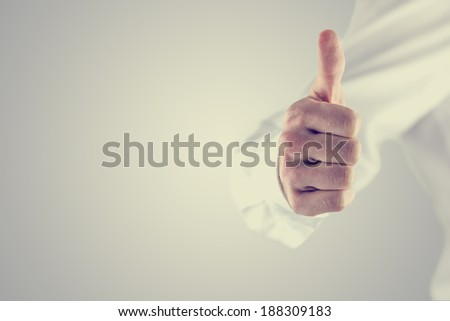 Retro vintage or instagram style image of a man giving a thumbs up gesture of approval and success on a grey background with copyspace.