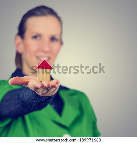 Retro vintage or instagram style image of a smiling young real estate agent holding out a model house on the palm of her hand conceptual of real estate. - stock photo