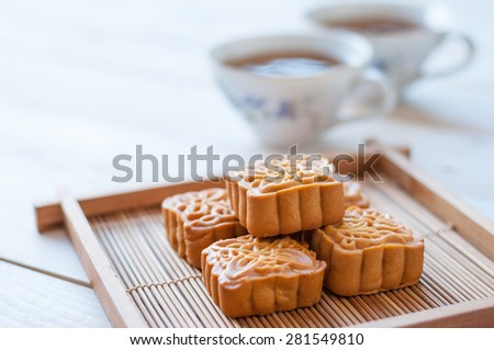 Retro vintage style Chinese mid autumn festival foods. Traditional mooncakes on table setting with teacup. - stock photo