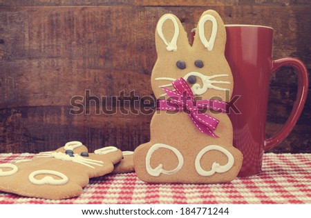 Retro vintage style Happy Easter bunny rabbit gingerbread cookies with coffee mug on red check table with dark wood recycled timber background. - stock photo