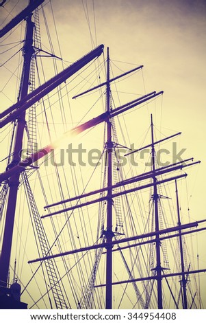 Retro vintage toned sailing masts at sunset, travel concept. - stock photo