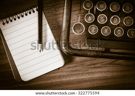 Retro vintage typewriter, pencil and notebook. Conceptual image of old fashioned office work, communication or writing. - stock photo